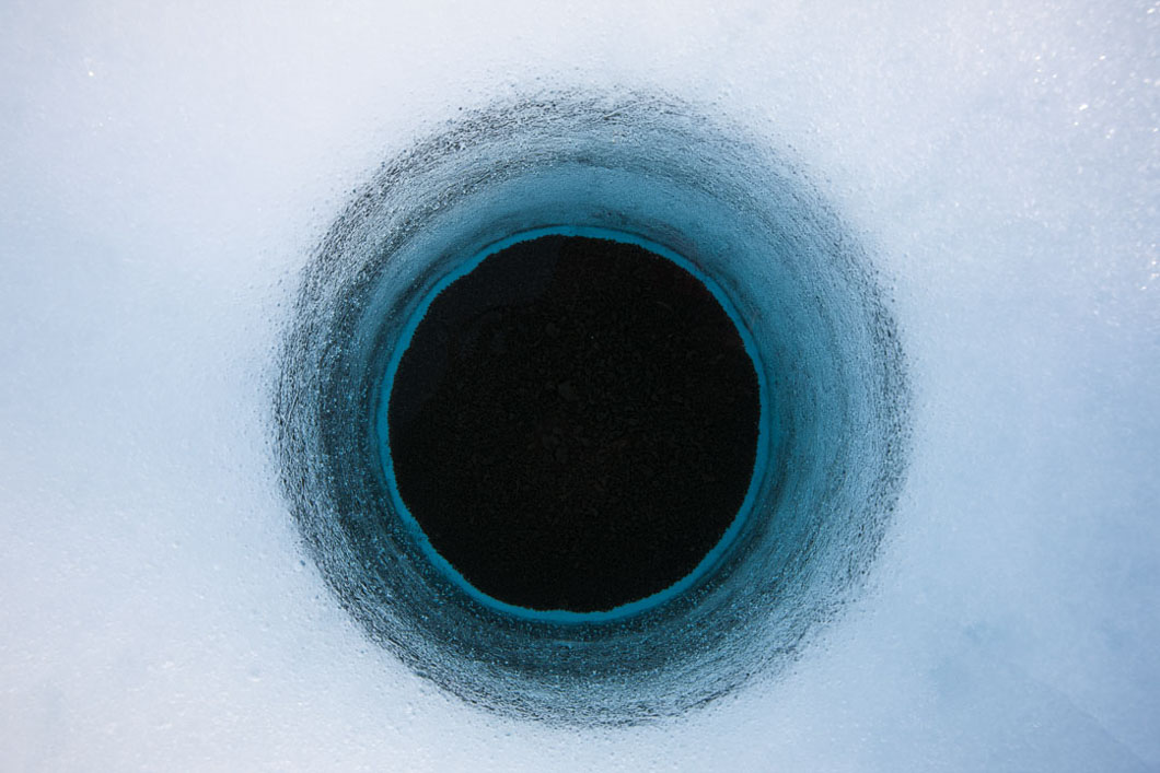 A hole on the bed of a melt lake, melted into the ice of Petermann Glacier. The brown material at the bottom of the hole is referred to as 'cryoconite' and is of particular interest to scientists. It lowers the 'albedo' of the ice -the ability to reflect radiant heat from the sun- because its colour is a darker part of the spectrum. The cryoconite which resembles a sludge or silt, absorbs more heat than the surrounding lighter coloured ice, which causes the ice underneath it to melt deeper causing the hole formation.