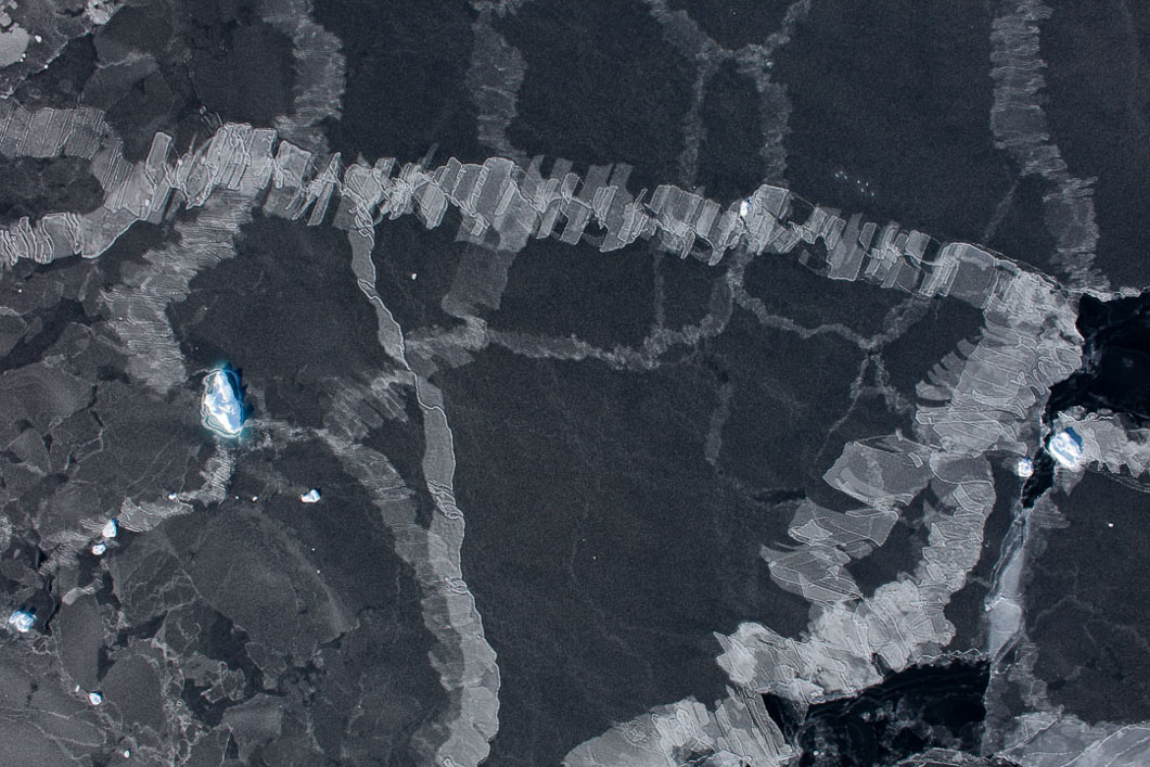 Finger rafting in sea ice photographed from the air. Finger rafting can be described as interlocking fingers of ice and occurs only in thin ice. It happens when the ice is pushed together by action of the wind on the ice's surface. There is a threshold of 10 cm; above which the ice will raft, but not make the delicate finger pattern.