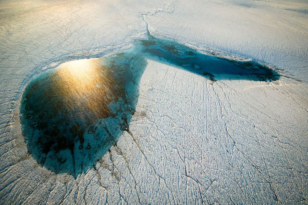A melt lake forms in the shape of a heart, visible from the air, a few miles inland of the edge of the Equip Sermia glacier that feeds into the fjord of Åta Sund near Disko Bay in South West Greenland. This one, measuring approximately 300 metres across, the tiny ravine at the top stretches back through the ice cap's surface. Photographed from the air using a tiny helicopter.