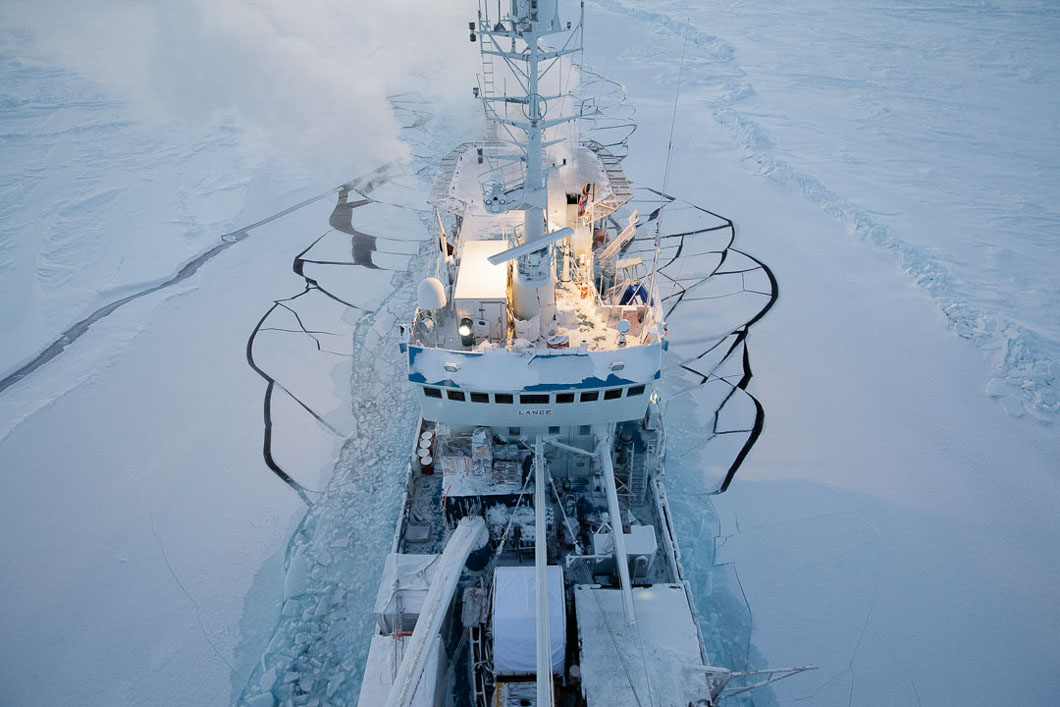 The Lance in Arctic sea ice 82 º N, photographed from high up in the rigging. This could be the last major trip for the Norwegian vessel, soon to be retired. She is an ex sealing ship built in 1978 in Kristiansund, Norway. She is well built and strong in the ice, but not technically not an icebreaker, so for this special project, deeper into the ice than usual, she has help from the larger more powerful coastguard ship. Right now the deck is crowded with boxes, cables and snow-scooters which are soon to be unloaded onto the ice for science work.