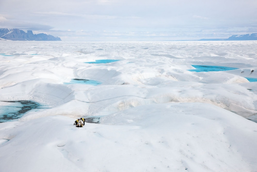 Two glaciologists fit a remote camera on Petermann Glacier, one of Greenland's largest and most northerly glaciers. They will later return to collect the data from the camera which is set to make a sequence of single images at time lapse periods.