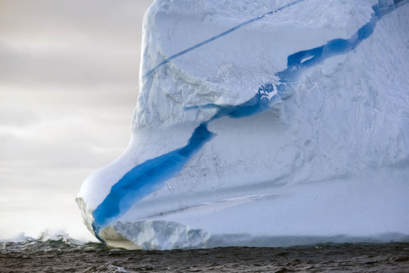A detailed shot of a line of dense ice inside an iceberg, floating in the sea off the south East Greenland coastline. The berg would have been calved from glaciers on Greenland. The strata of different coloured ice appears blue because it has a different density to the ice surrounding it. Possibly a meltwater ravine that had frozen solid in the glacier before the berg was calved.