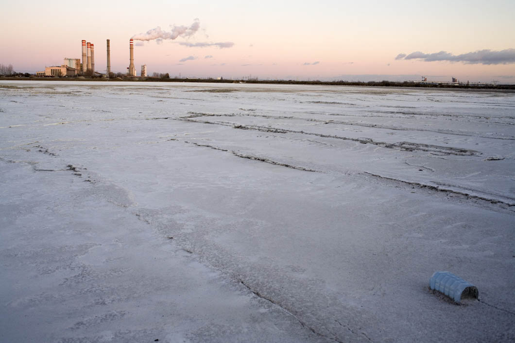 The town of Goslawice near Konin is overlooked by the two coal fired power stations, pictured here is Elektrownia Konin. Pipes discharge a mixture of water and waste ash which is a waste product from the power station into shallow craters in the ground behind the village. The result resembles lakes of a white ash based sludge, stretching out in front of the power station.