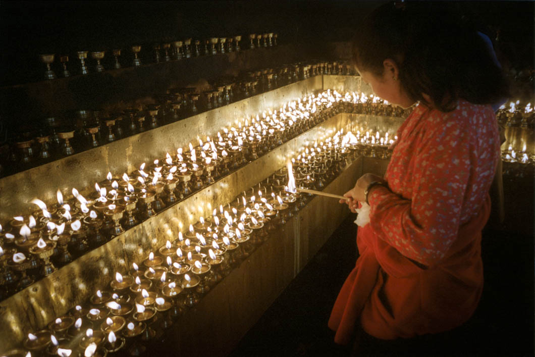 A visitor to the undergound bunker where ceremonial candles from the Jokhang Temple have been located. The rows of candles are kept lit by hundreds of visitors who cross the Jokhang Square in centra Lhasa. They were removed from the Jokhang -An important Budhist temple and shrine, by the Chinese under a UN sponsored initiative, supposedly to limit the risk of fire damage to the ancient building.