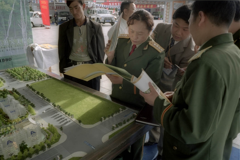 Members of China's People's Liberation Army (PLA) look through sales literature around a marketing stall that sells real-estate in nearby Chengdu. The stall is part of a trade fair in the middle of the Potala Square, overlooked by the famous palace of the Dalai Lama.