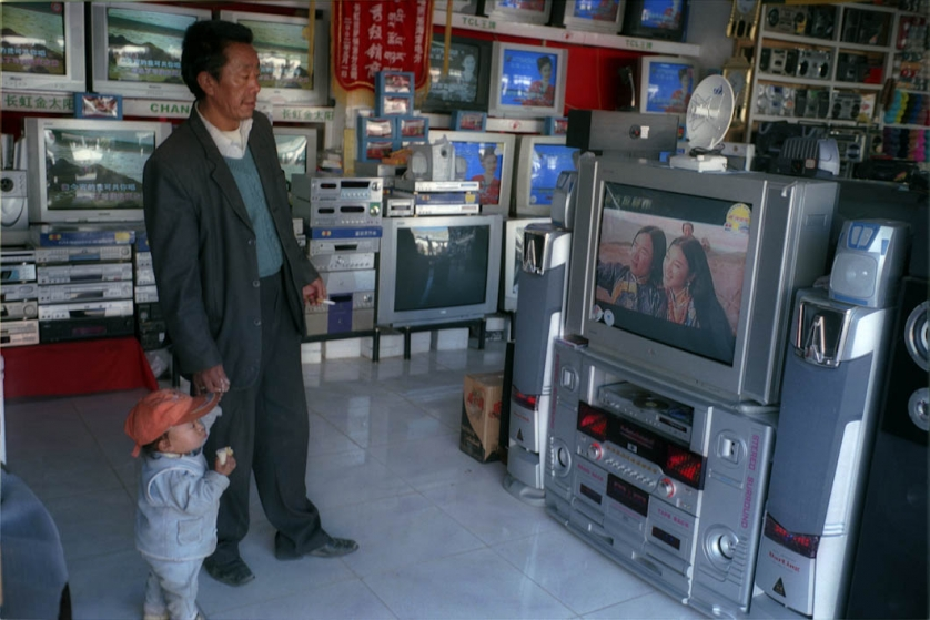 A man and his son browse in an electronics shop in central Shigatse, a town in Tibet. Western shops like this have made in-roads into the traditional culture of Tibet.