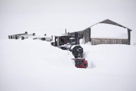 Coal train in deep snow at Ny-Ålesund on the coastline of Svalbard